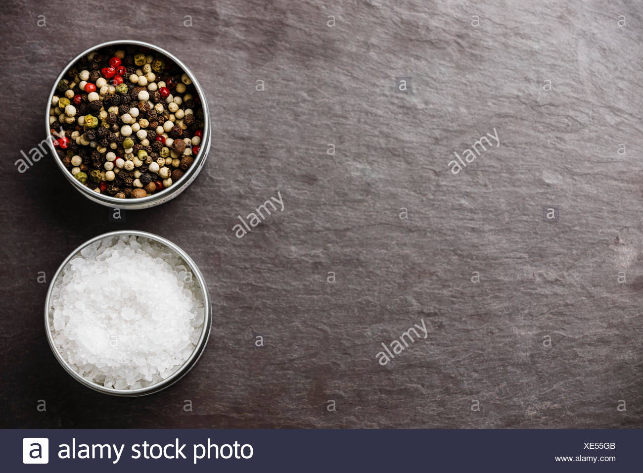 Stone slate background with Sea salt and Multicolored pepper in metal boxes - Stock Image