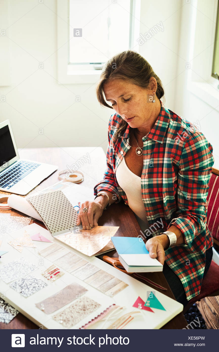 A woman looking at colour and design and collage of patterns. Laptop on desk. - Stock Image