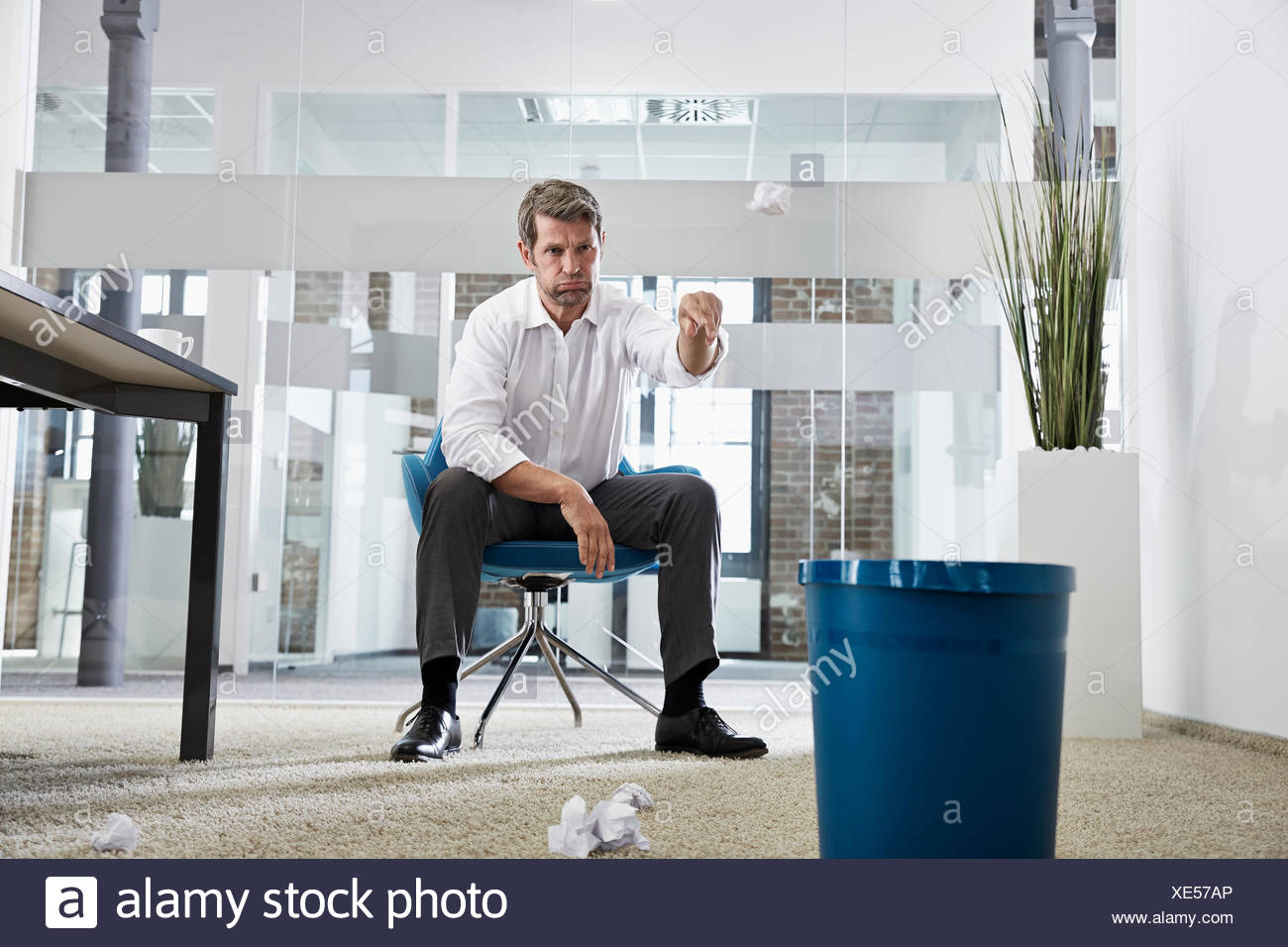 Businessman in office throwing crumpled paper in wastepaper basket - Stock Image