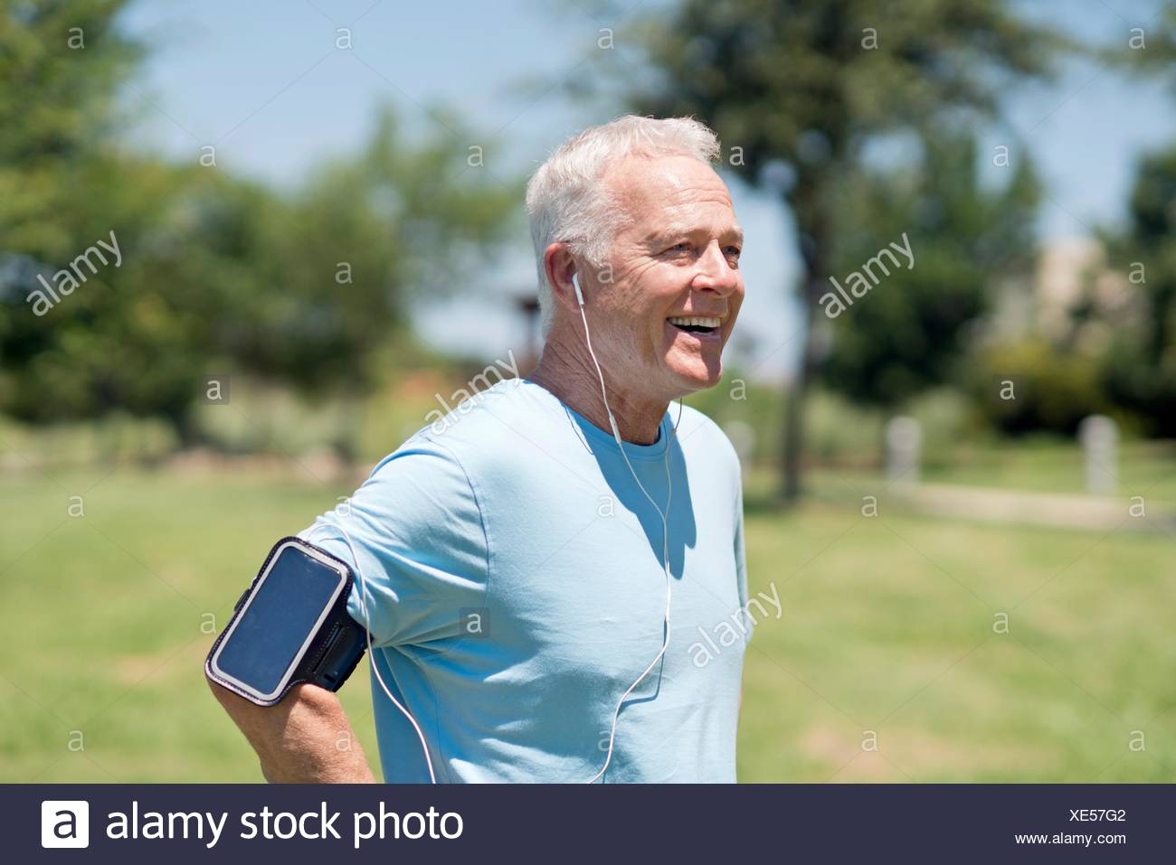Senior man wearing smartphone on arm and earphones in park. - Stock Image