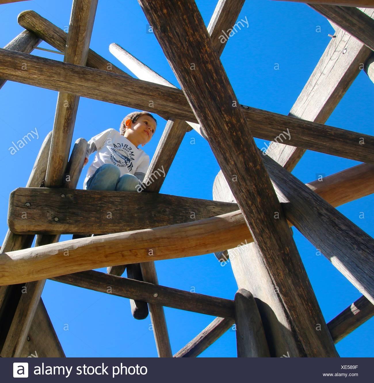 Italy, Trentino-Alto Adige, Alto Adige, Bolzano, Low angle view of boy (4-5) playing on wooden playground - Stock Image