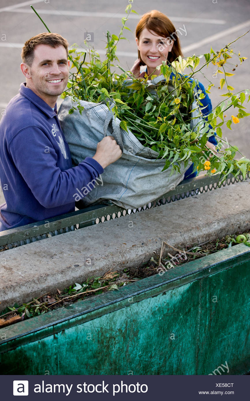 A mid-adult couple disposing of garden waste in a recycling center - Stock Image