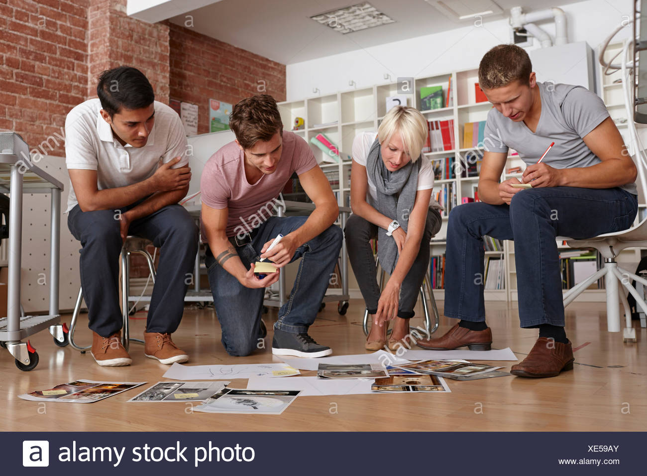 Colleagues in meeting looking at papers on floor - Stock Image