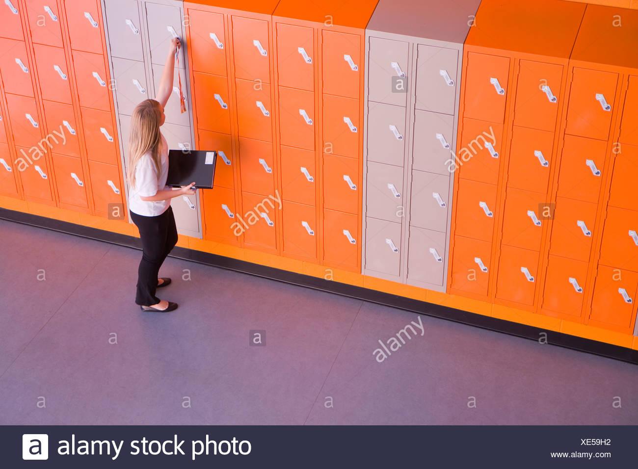 Girl opening locker in school corridor - Stock Image