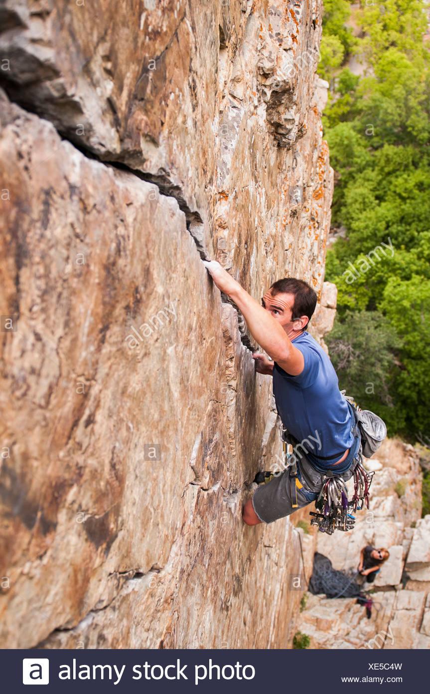 Rock climber scaling boulder crack - Stock Image