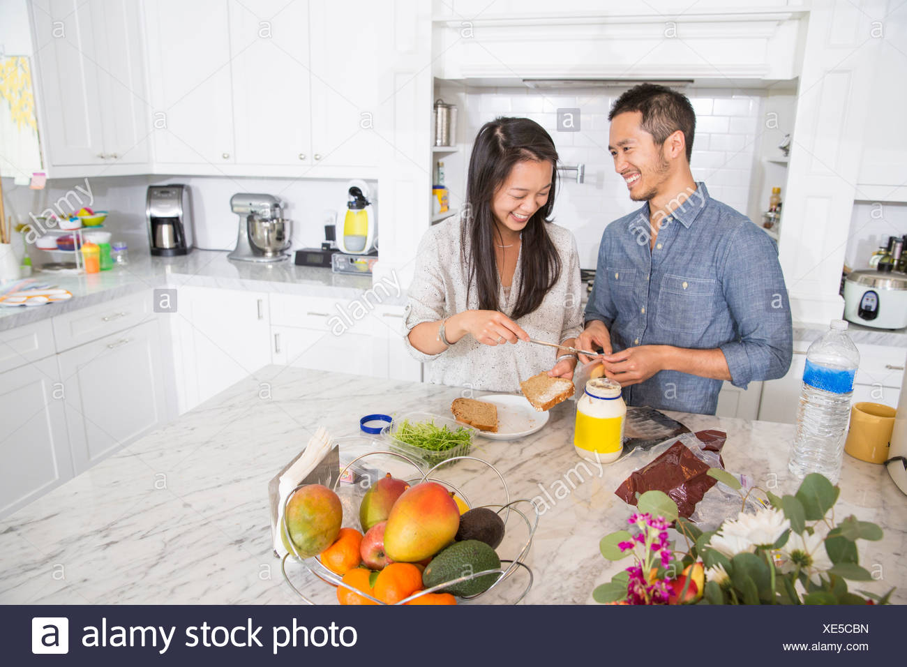 Mid adult couple preparing sandwich in kitchen - Stock Image