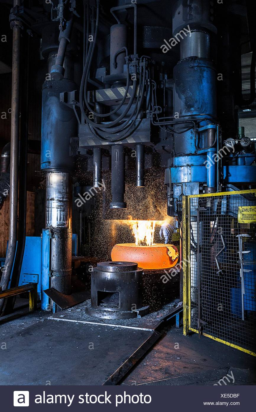 Manufacturing machine shaping red hot steel in foundry - Stock Image