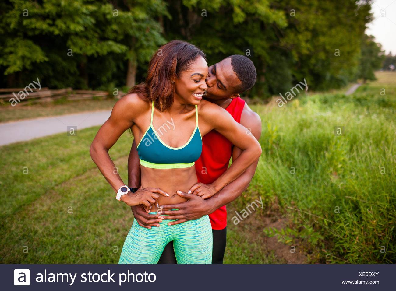 Portrait of romantic young couple training by rural road - Stock Image