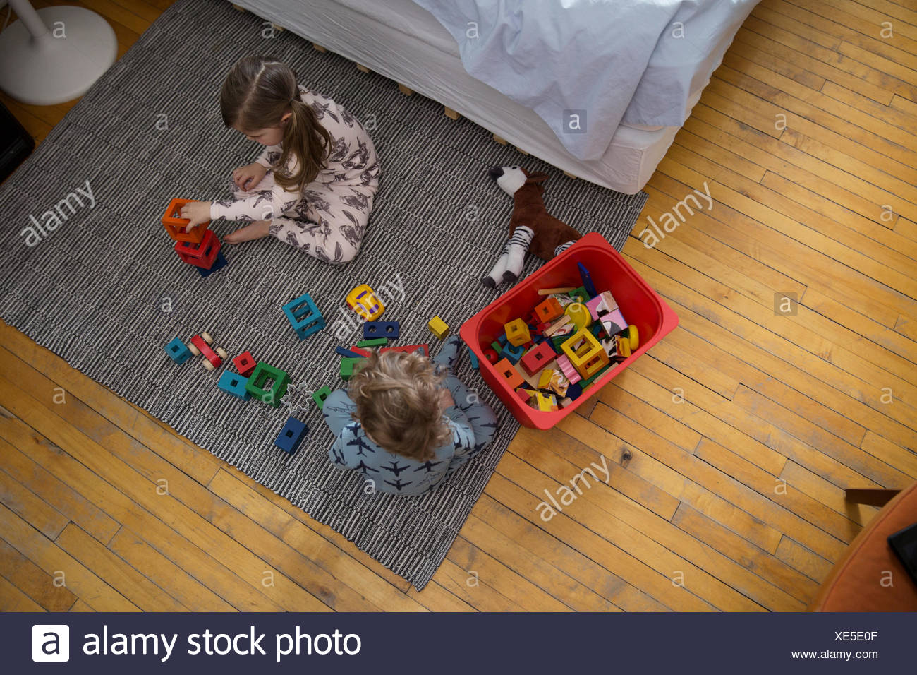 Children in pajamas playing with toys on floor - Stock Image