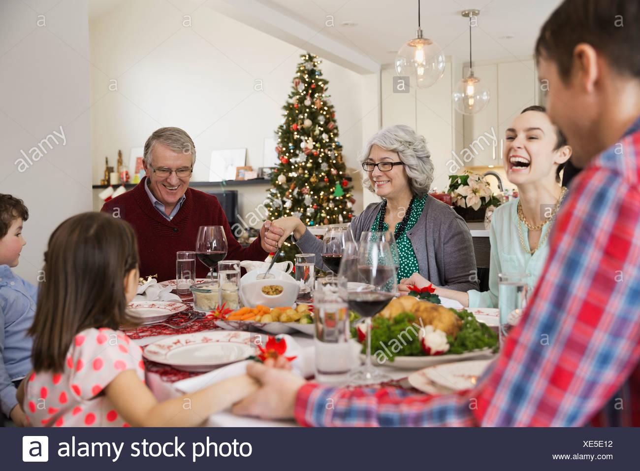 Multi-generation family saying grace before Christmas dinner - Stock Image