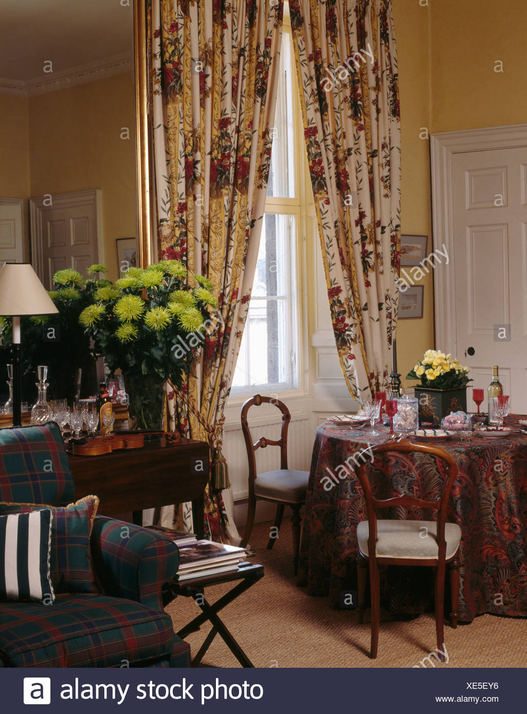 Red cream patterned curtains in dining room with lime green chrysanthemums in vase on table in front of mirror Stock Photo