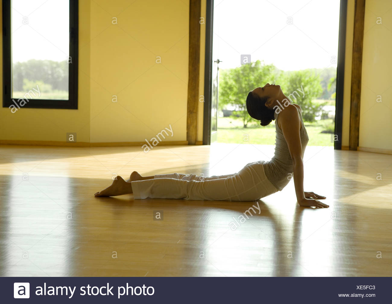 Woman doing cobra pose, side view - Stock Image