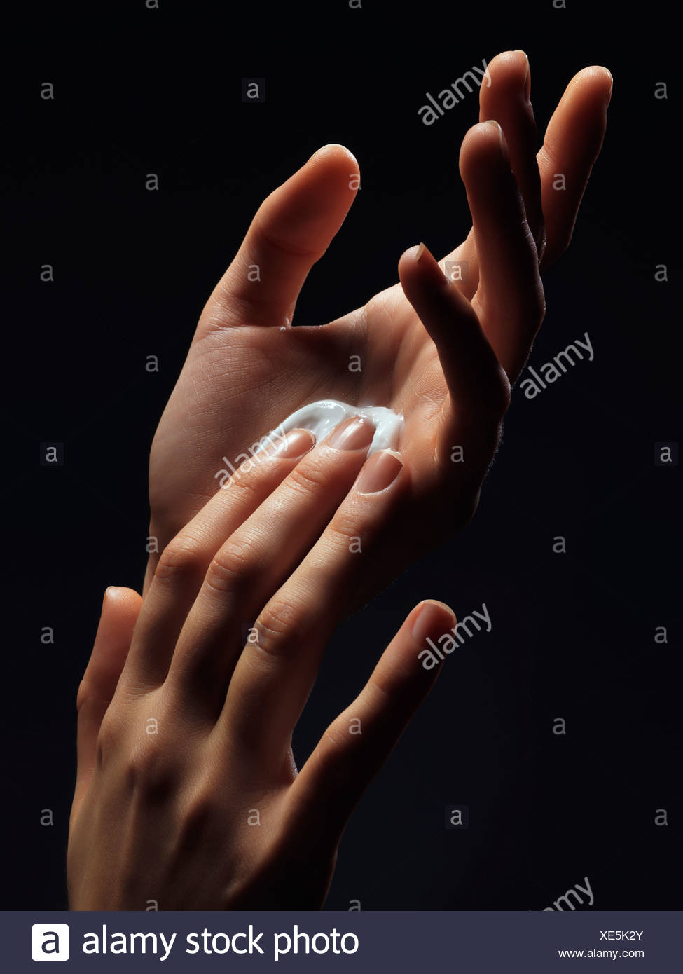 Close up of womans hands with lotion - Stock Image
