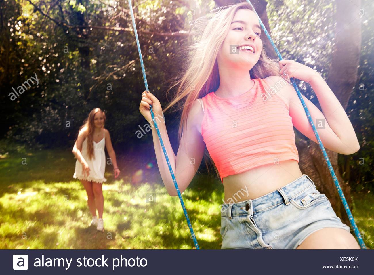 Teenage girl pushing her friend on tree swing - Stock Image
