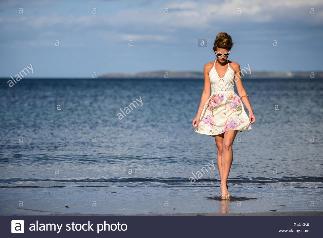 Young woman walking along the beach - Stock Image