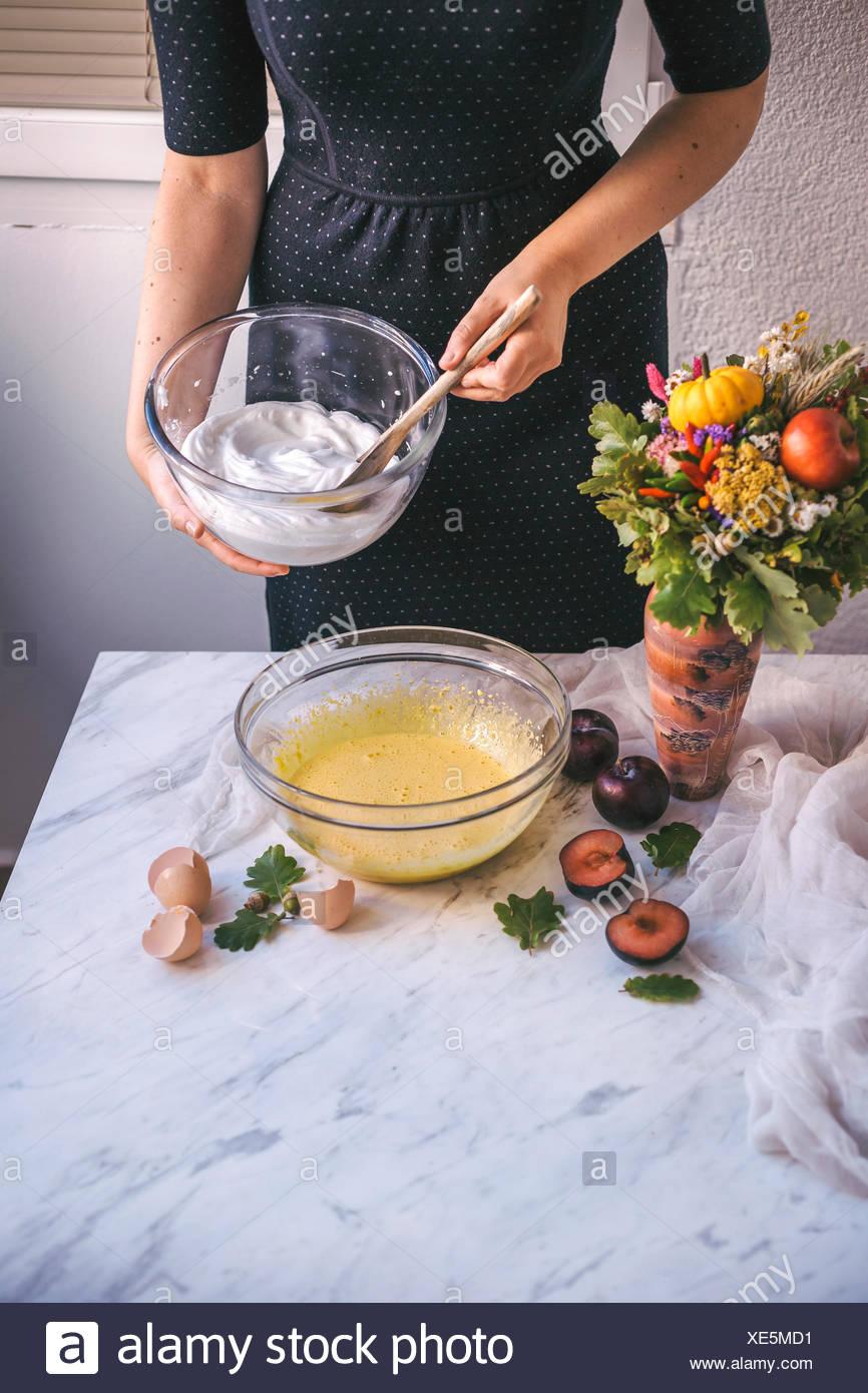 Woman holding a bowl of beaten egg whites while baking a cake - Stock Image
