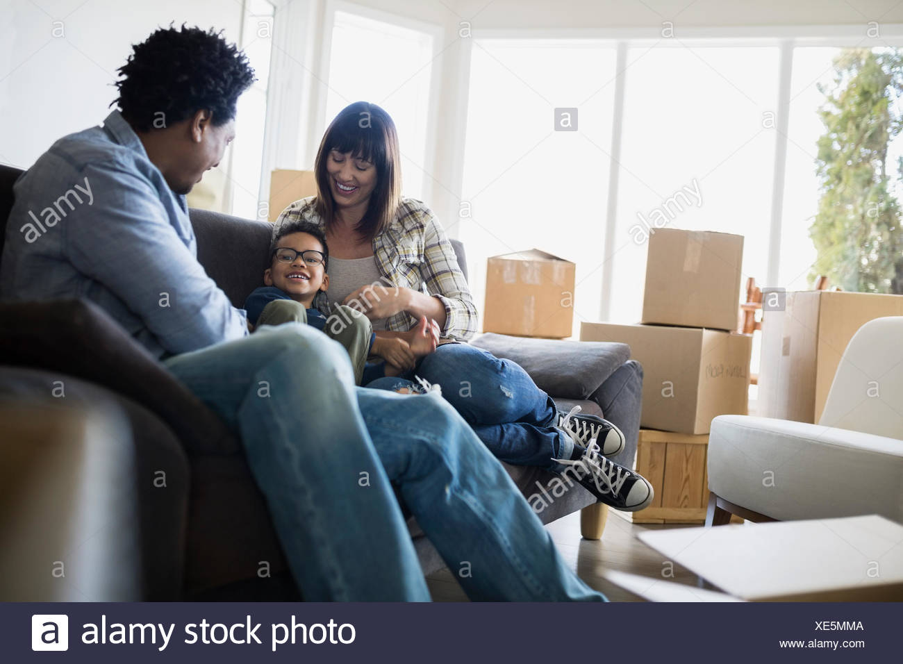 Moving boxes surrounding family relaxing on sofa - Stock Image
