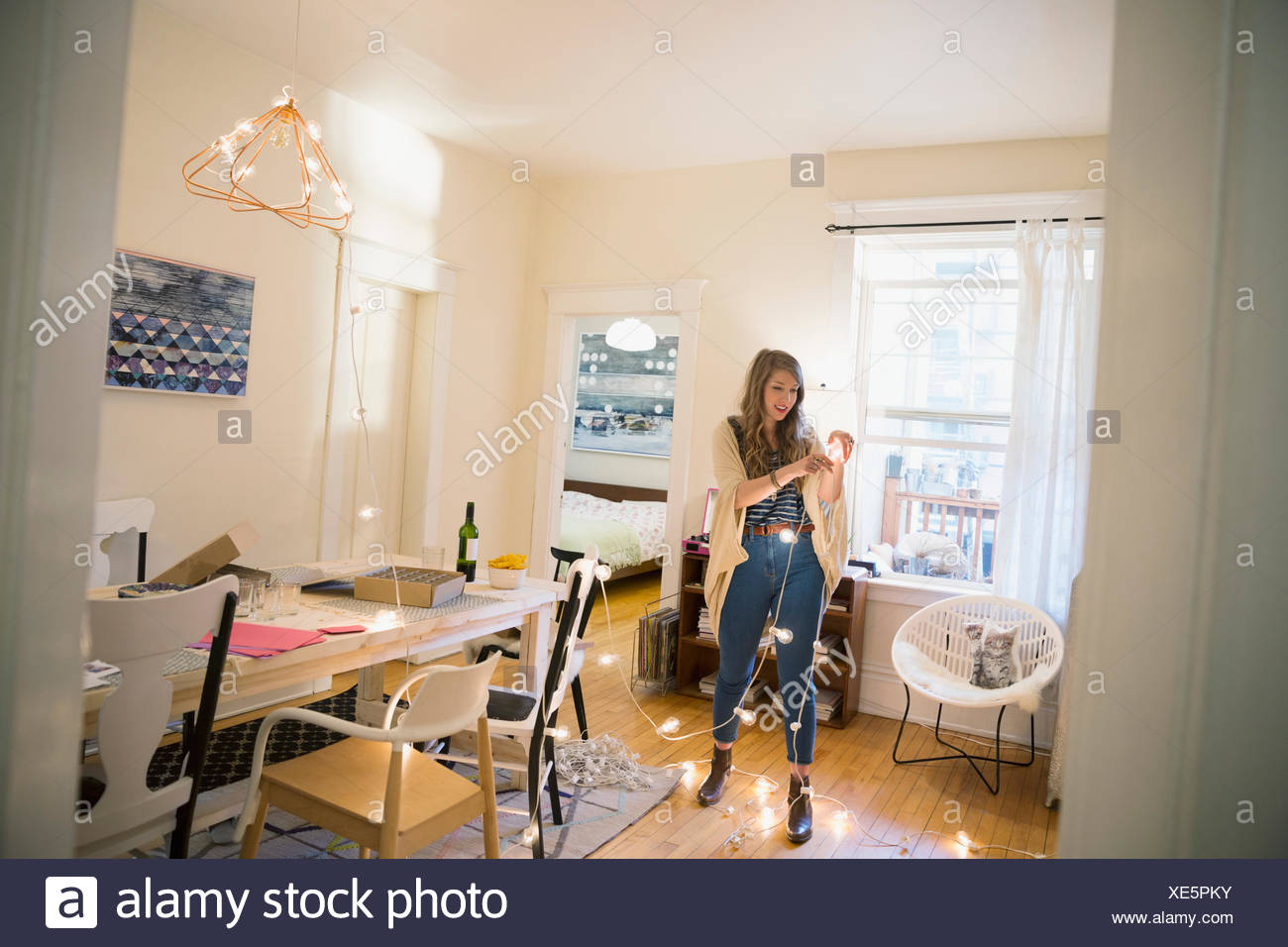 Woman hanging string lights in dining room Stock Photo