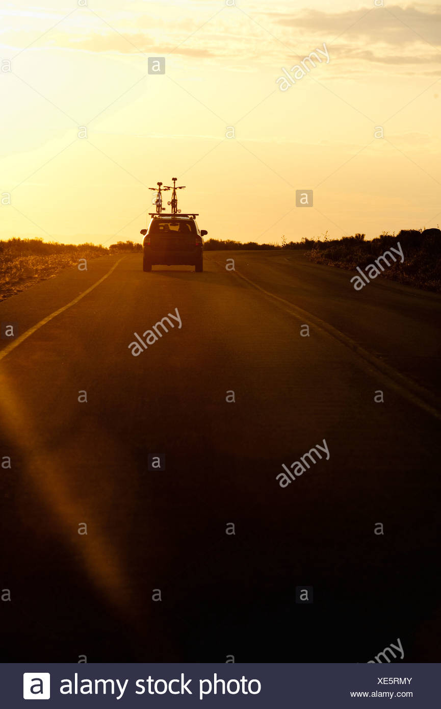 A car with two bikes on top drives towards a sunset on Antelope Island, UT. - Stock Image