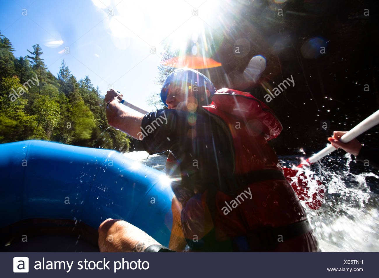 A young man paddles down a river while whitewater rafting. - Stock Image