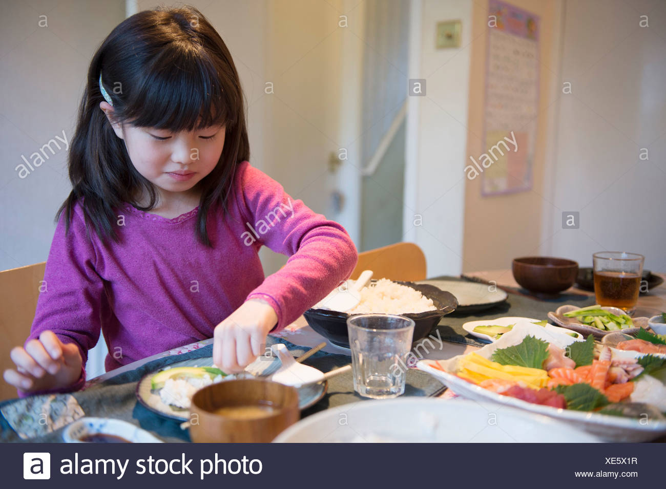Girl selecting meal from dishes on dining table - Stock Image