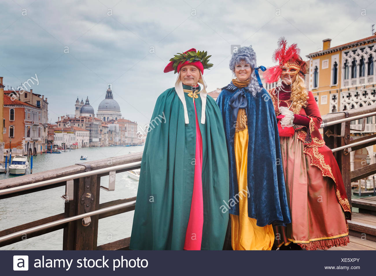 Europe, Italy, Veneto, Venice. Group of people in carnival fancy dress on the Accademia bridge Stock Photo
