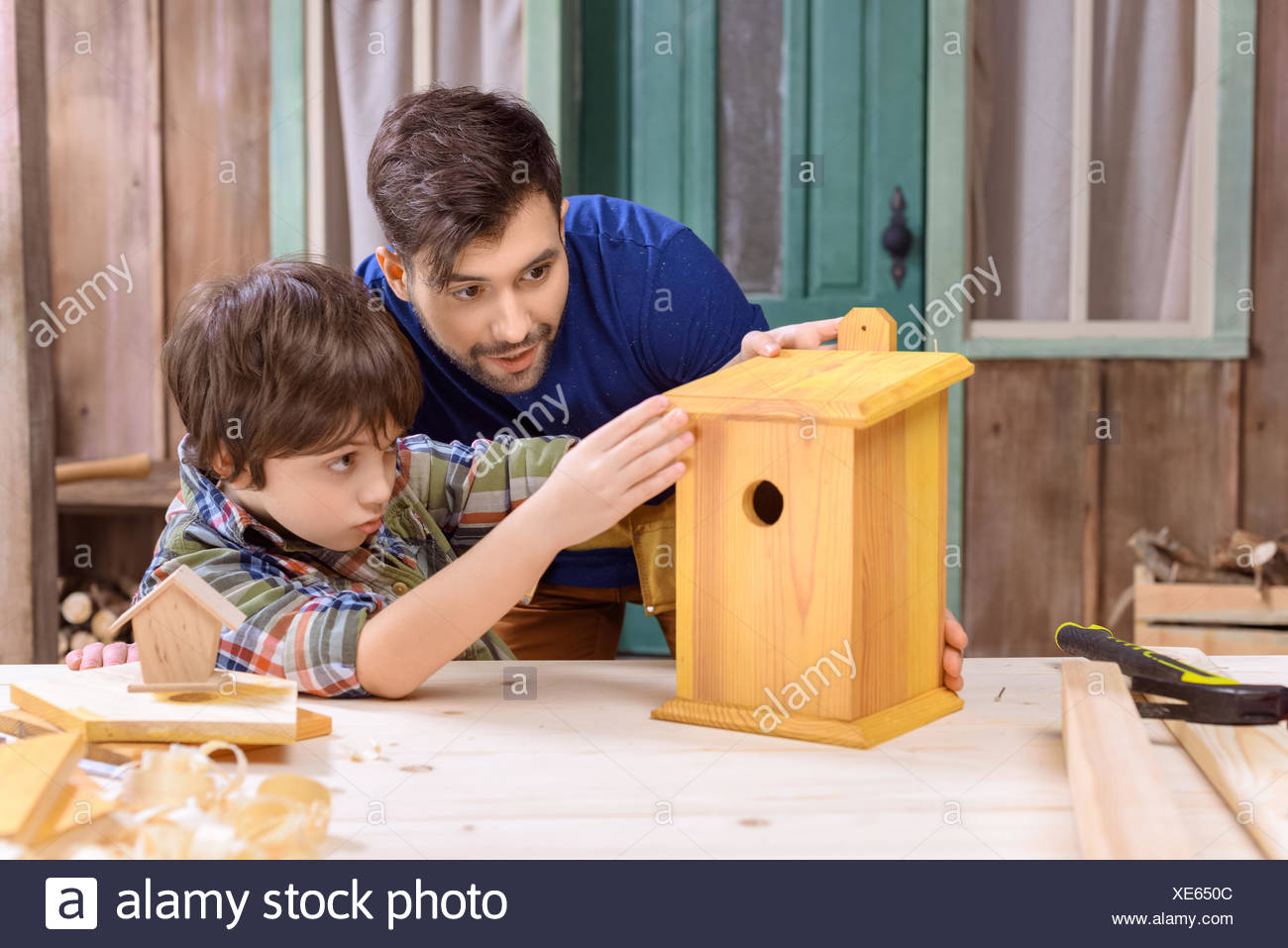 Concentrated father and son making wooden birdhouse together in workshop - Stock Image