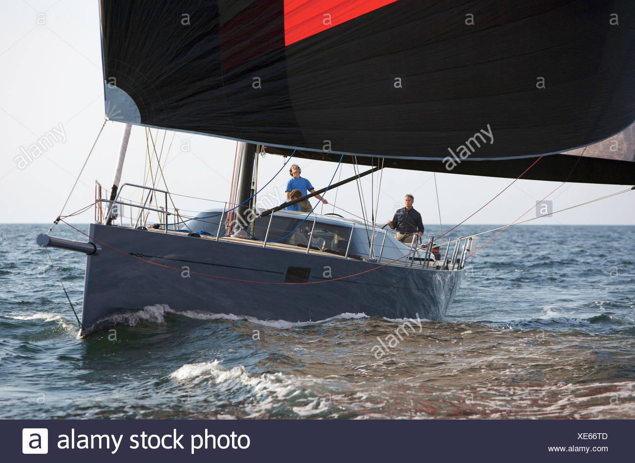 A crew races a modern ocean-going sailing yacht under spinnaker. - Stock Image