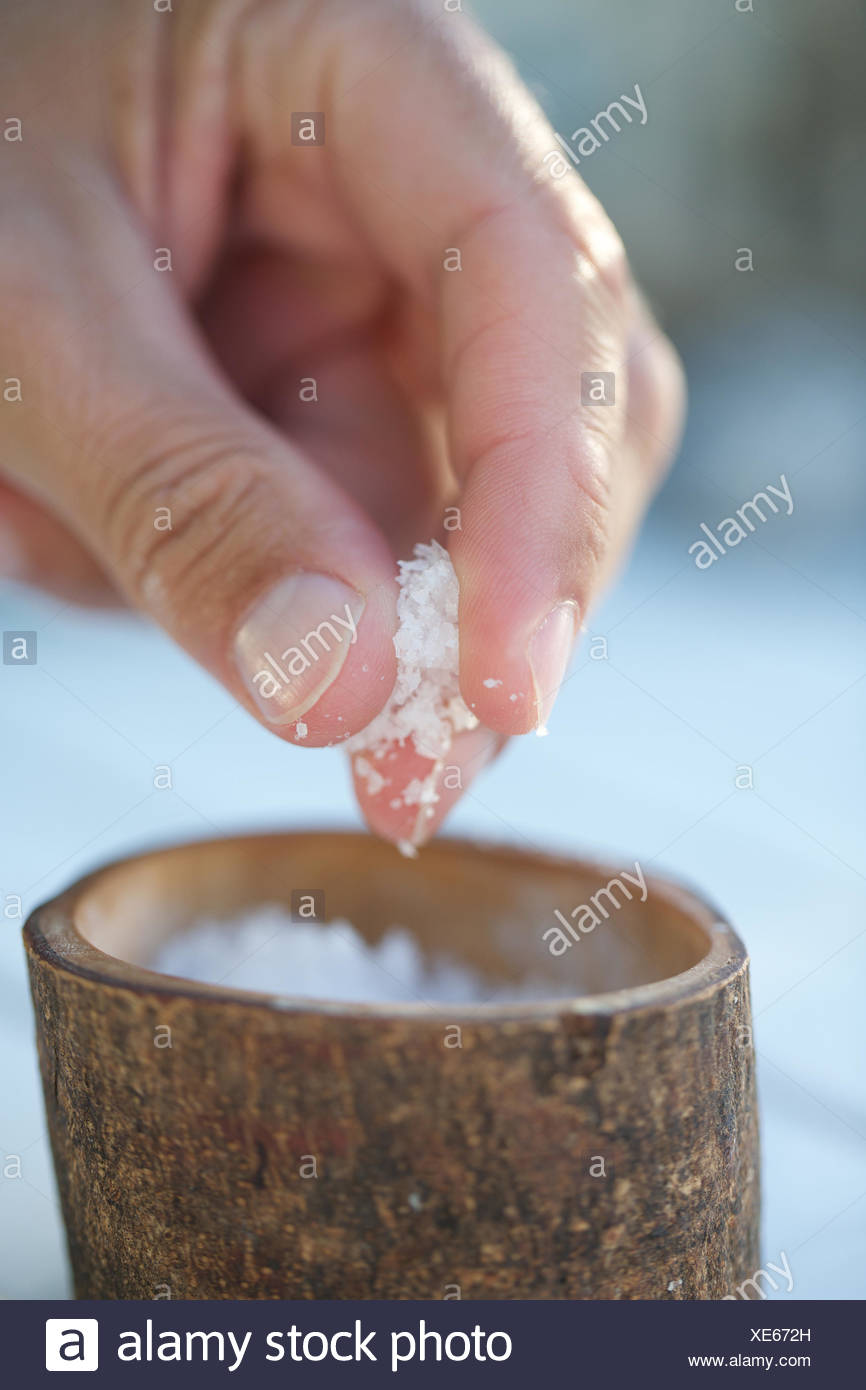 hand taking a pinch of salt from container. mineral, hand, pinch, sea salt. - Stock Image