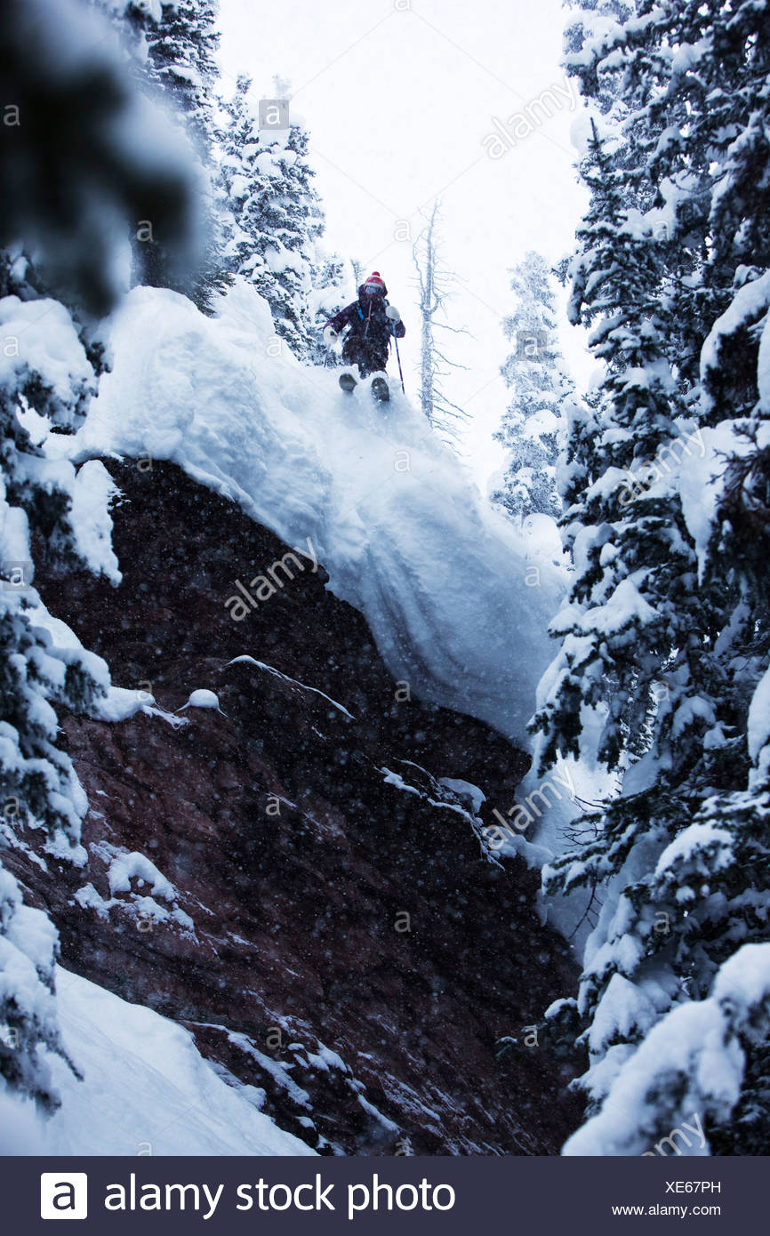 A athletic skier jumping off a cliff in the backcountry on a stormy day in Colorado. - Stock Image