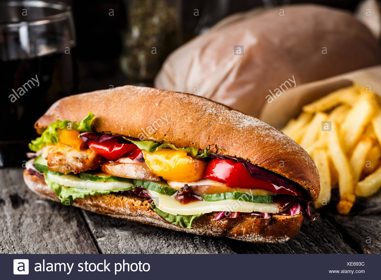 Chicken sandwich, fries and glass of soda on a rustic table - Stock Image