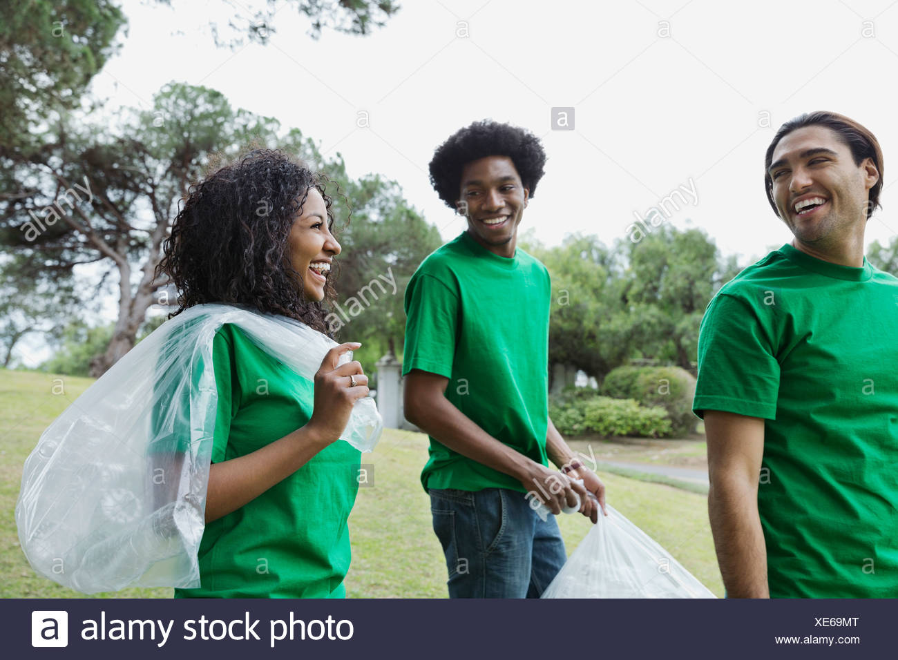 Happy environmentalists with plastic bags in park - Stock Image