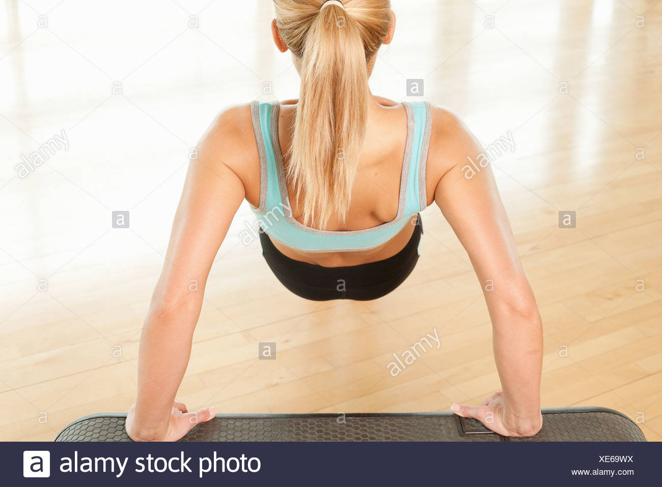 Rear view of woman doing press ups on step - Stock Image
