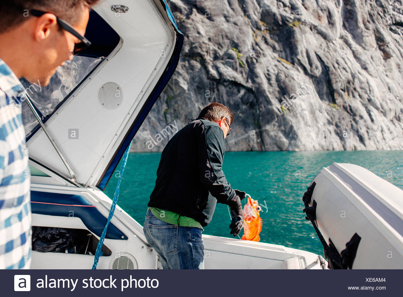 Men standing on nautical vessel and fishing at sea - Stock Image