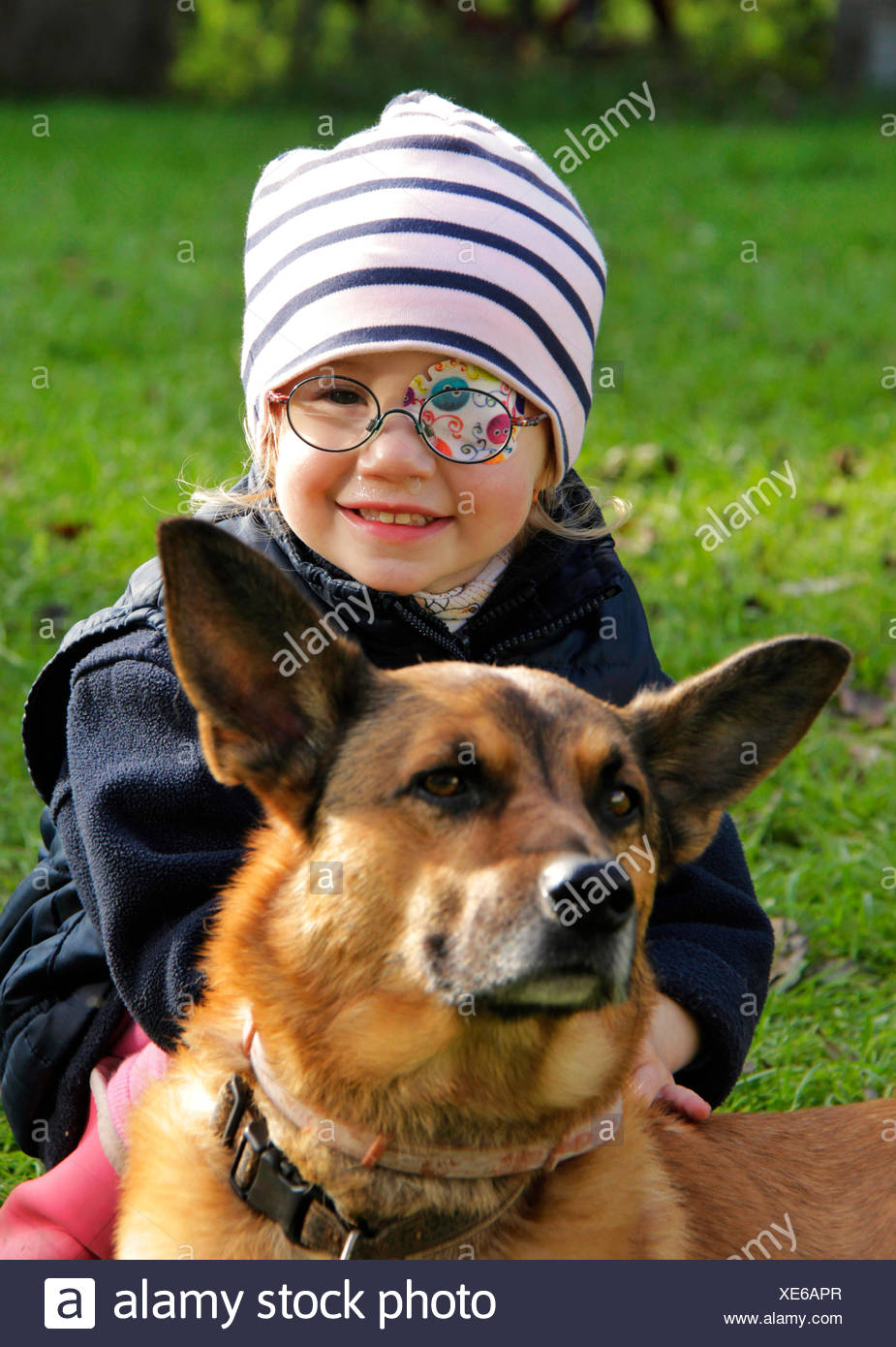 mixed breed dog (Canis lupus f. familiaris), little girl with eye patch stroking a dog, Germany - Stock Image