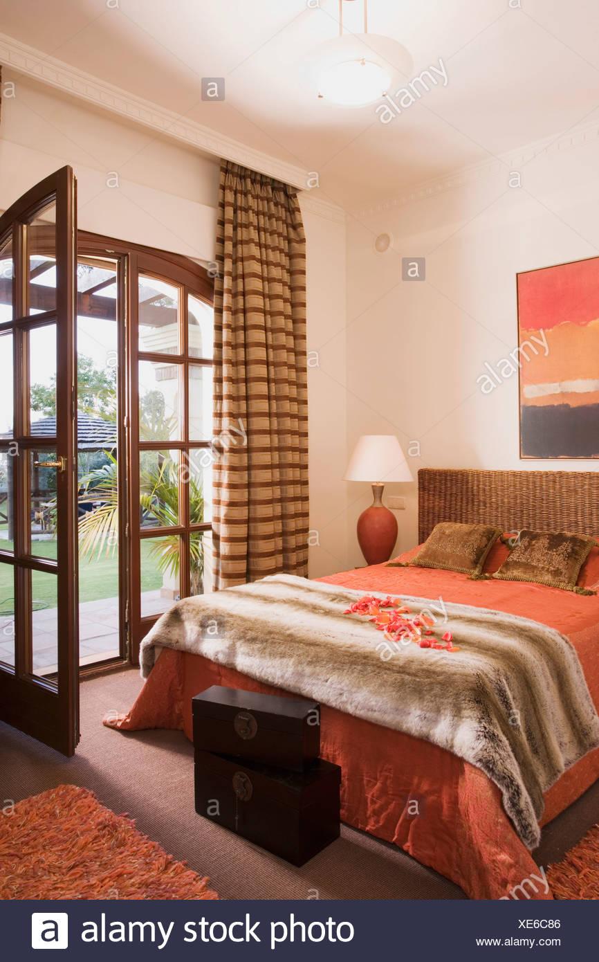 Artificial fur throw on bed with orange bedlinen in Spanish bedroom ...