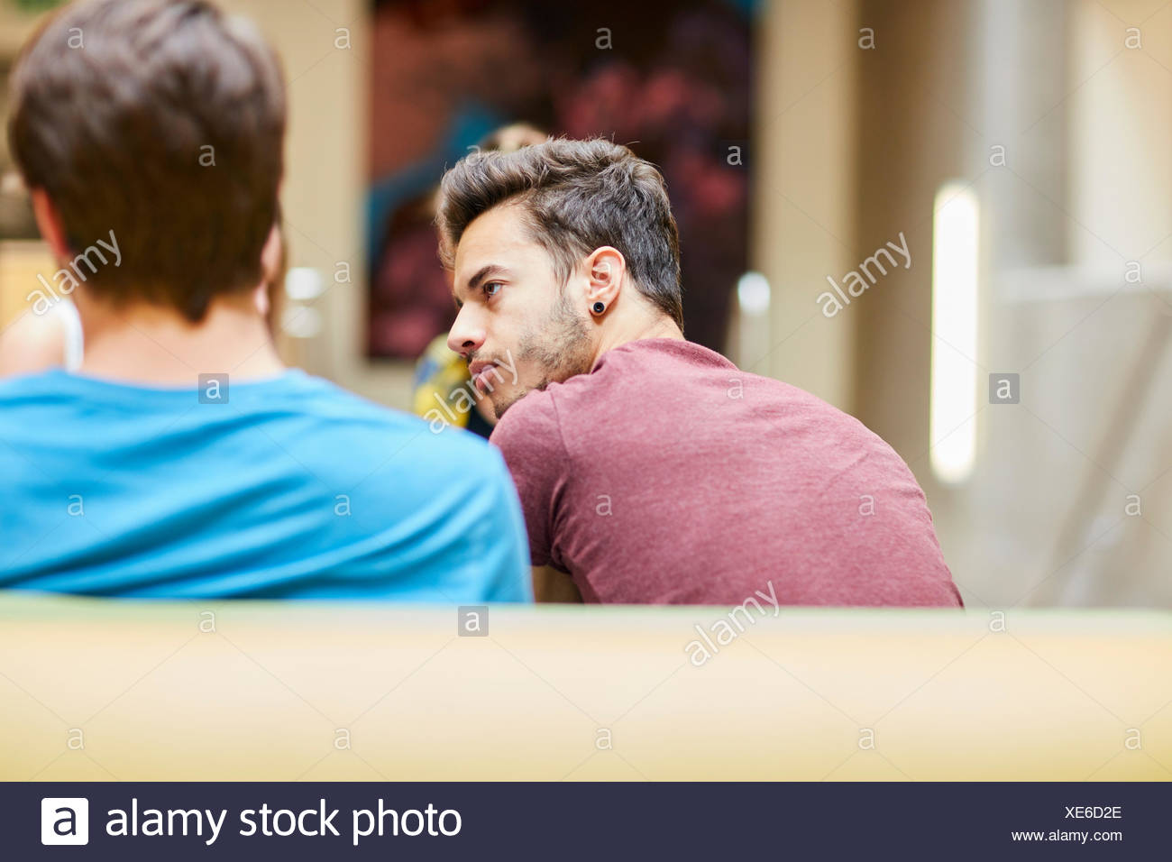 Rear view of male students in canteen at higher education college - Stock Image