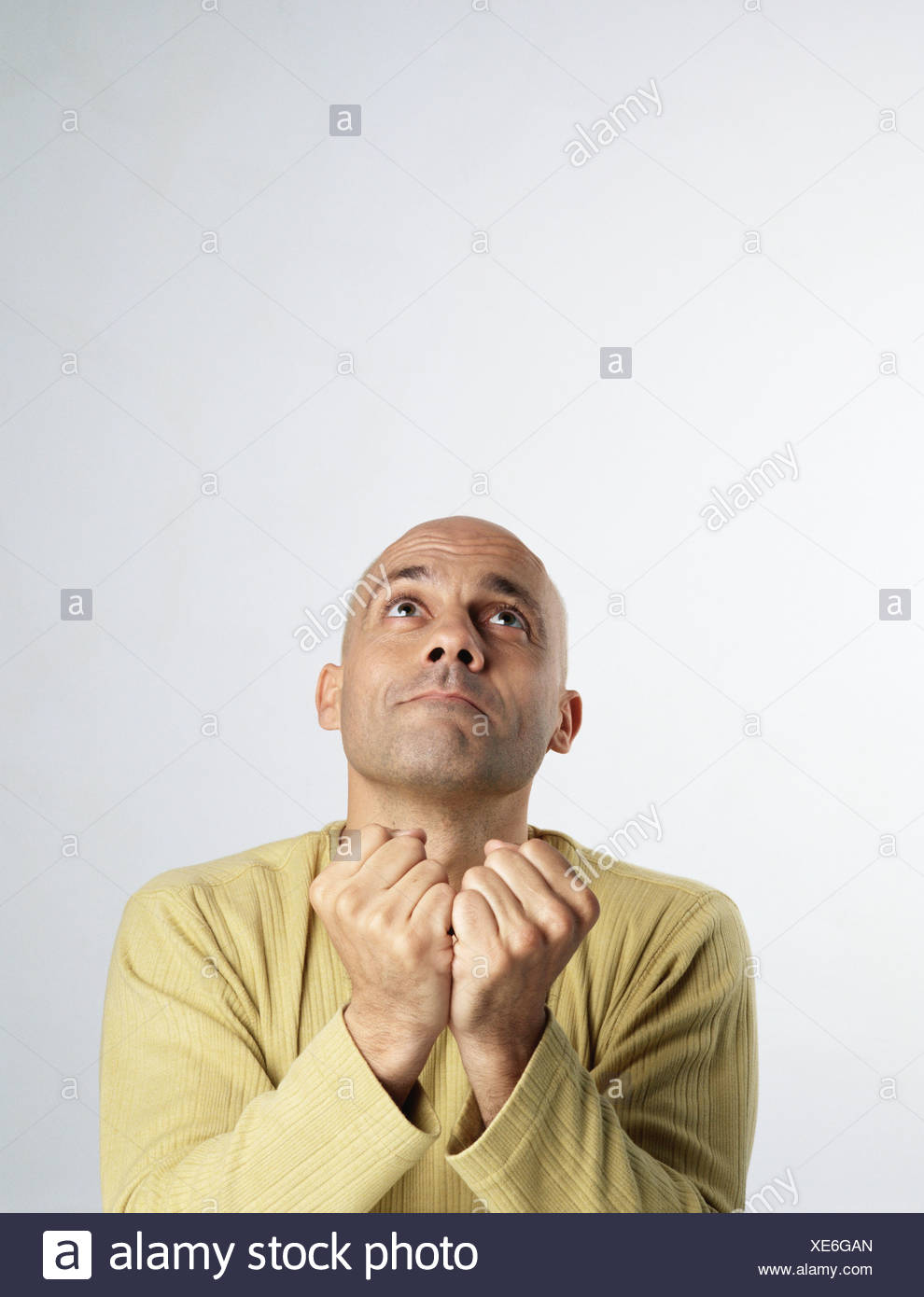 Man looking up, holding fists togther in front of him - Stock Image