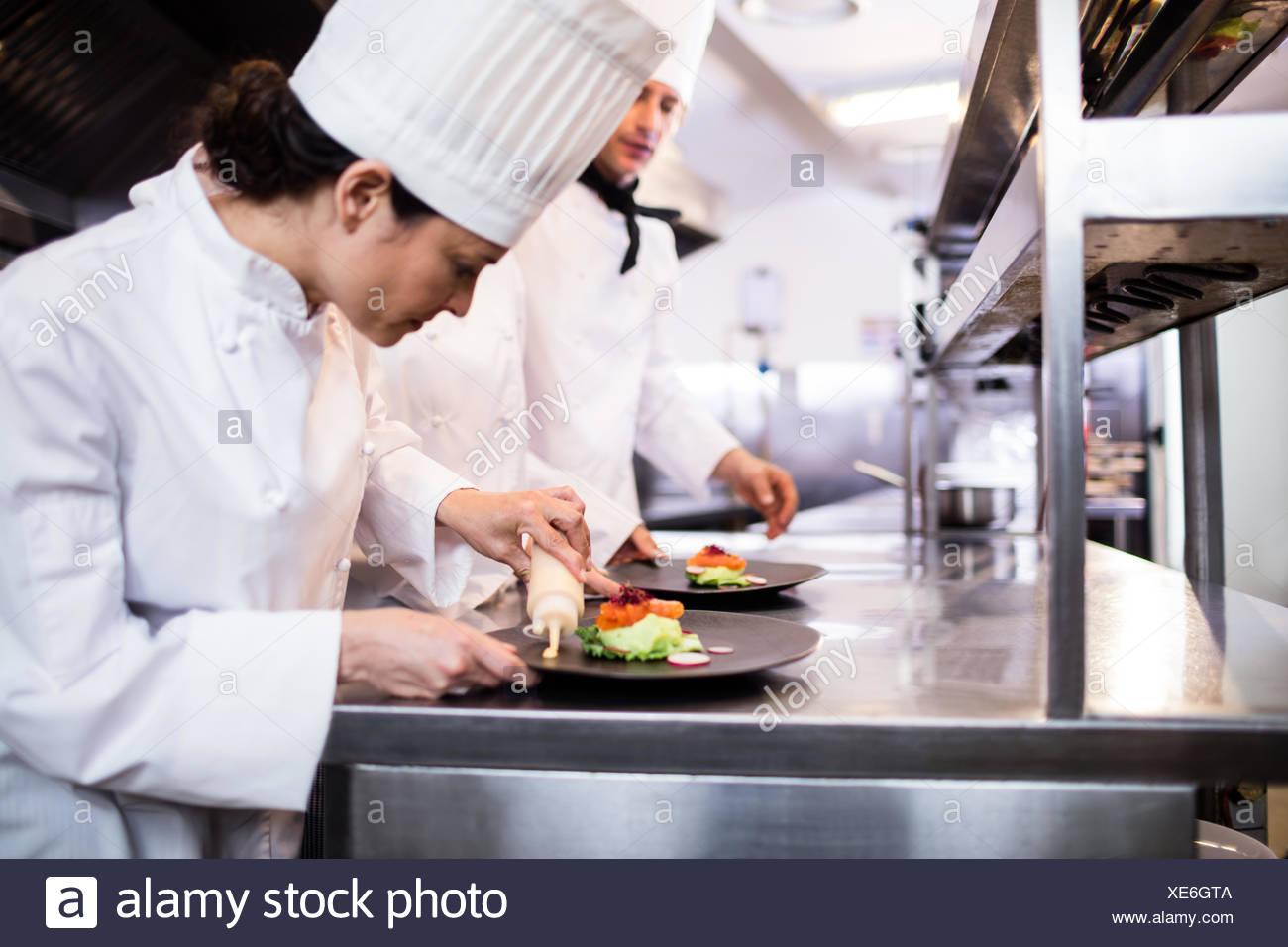 Chef decorating a food plate - Stock Image