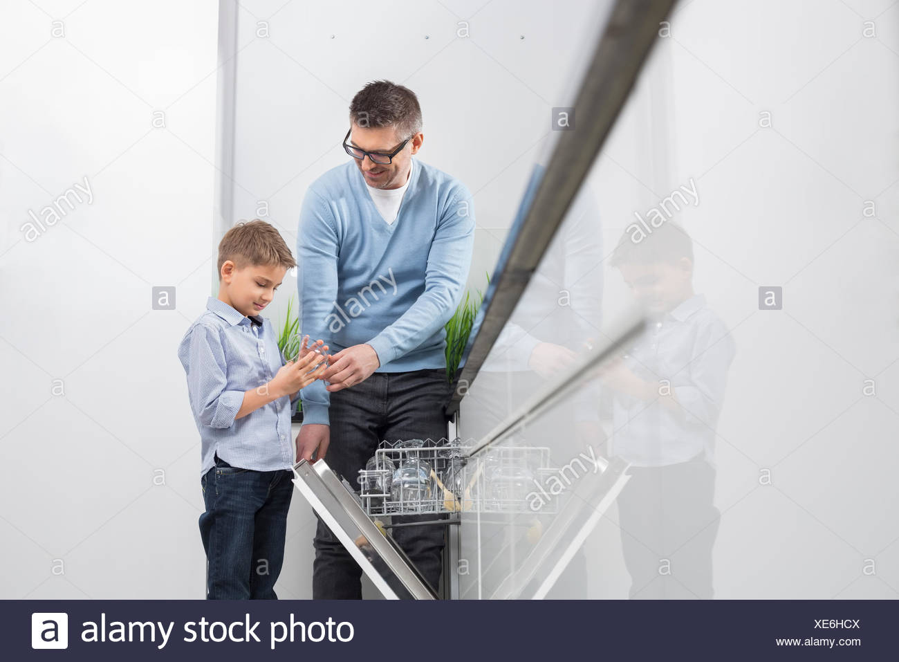 Father and son placing glass in dishwasher at kitchen - Stock Image