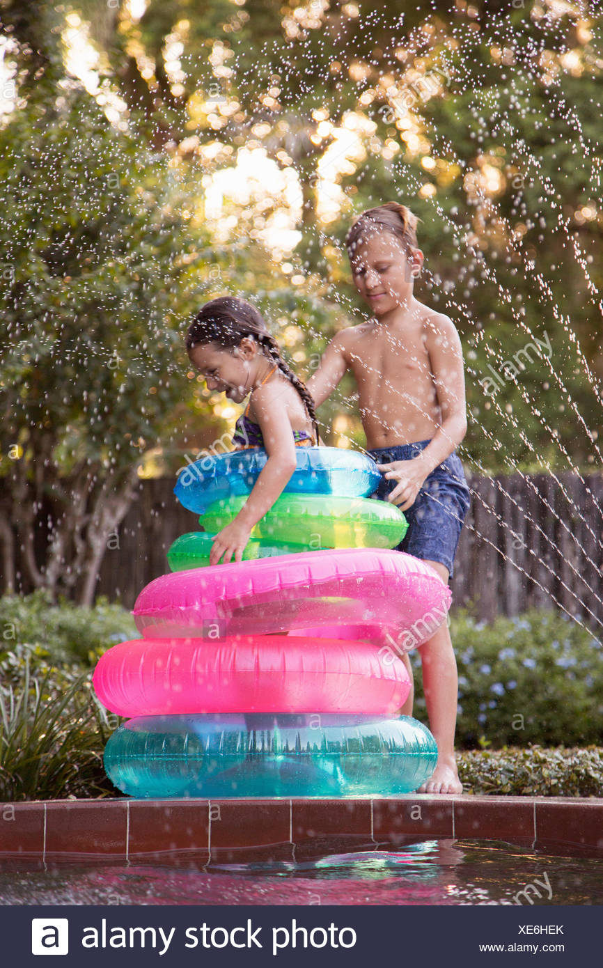Young girl, standing in the middle of inflatable rings on the side of outdoor swimming pool, brother stacking rings Stock Photo