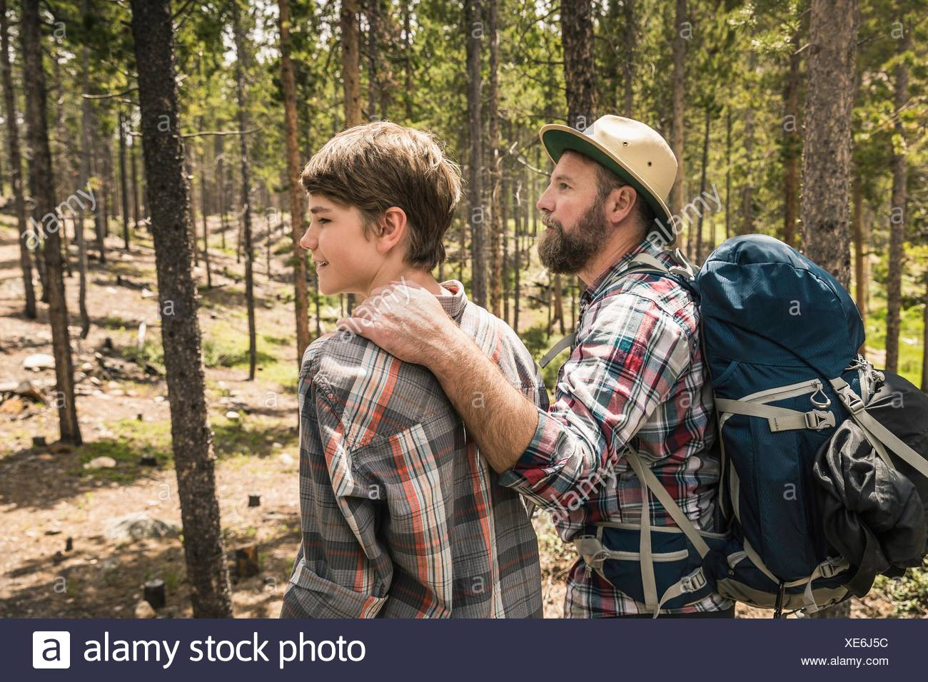 Side view of father with hand on sons shoulder trekking through forest, Red Lodge, Montana, USA - Stock Image