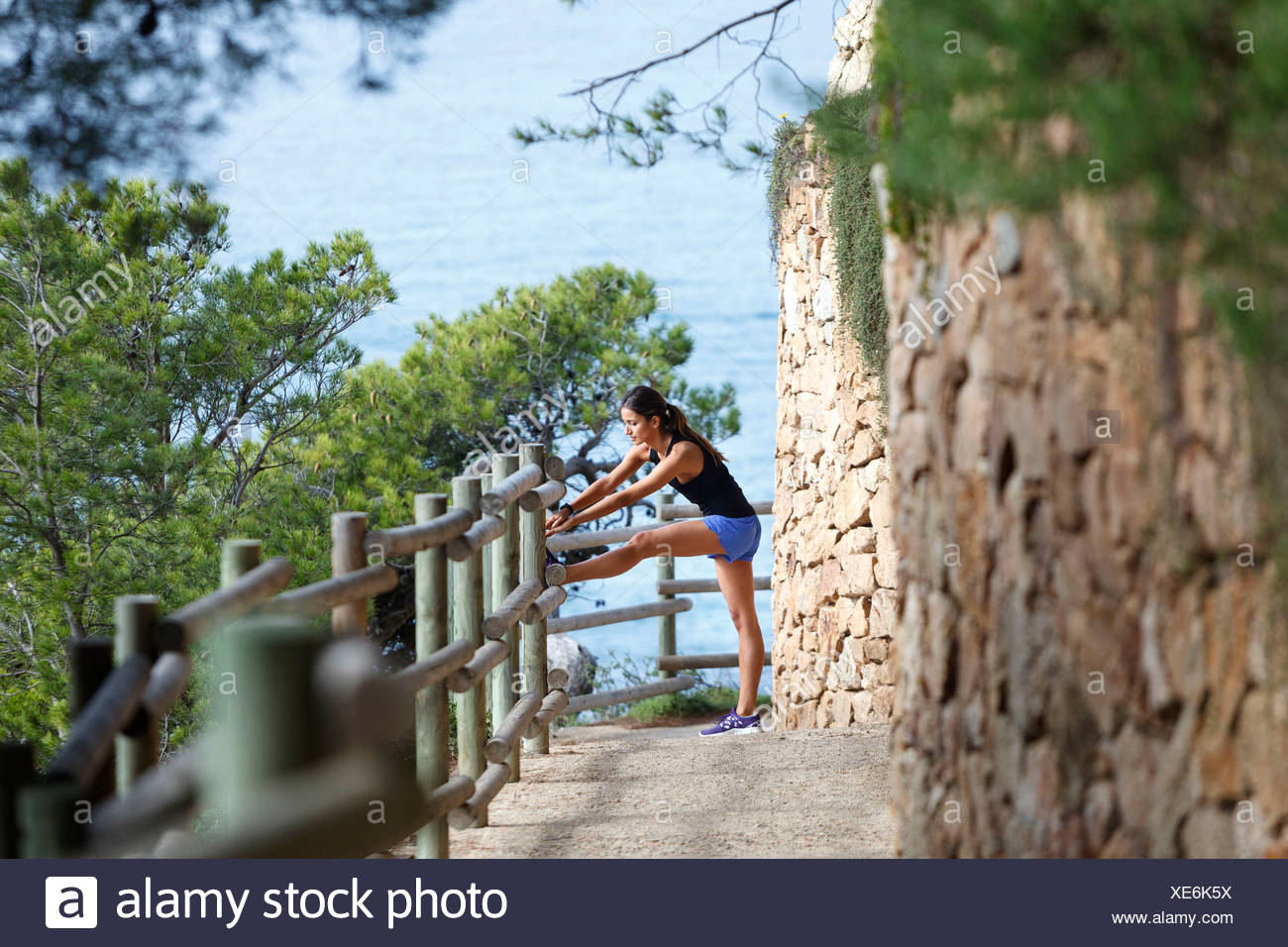 Runner stretching on dirt path - Stock Image