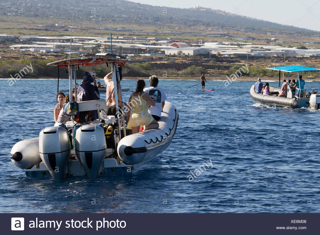 Dolphin and whale watching boats with tourists and a stand-up paddleboarder off the Kona coast - Stock Image