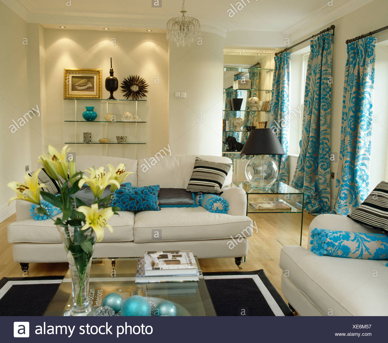 Recessed lighting above alcove shelving in cream living room with turquoise cushions on white sofas - Stock Image