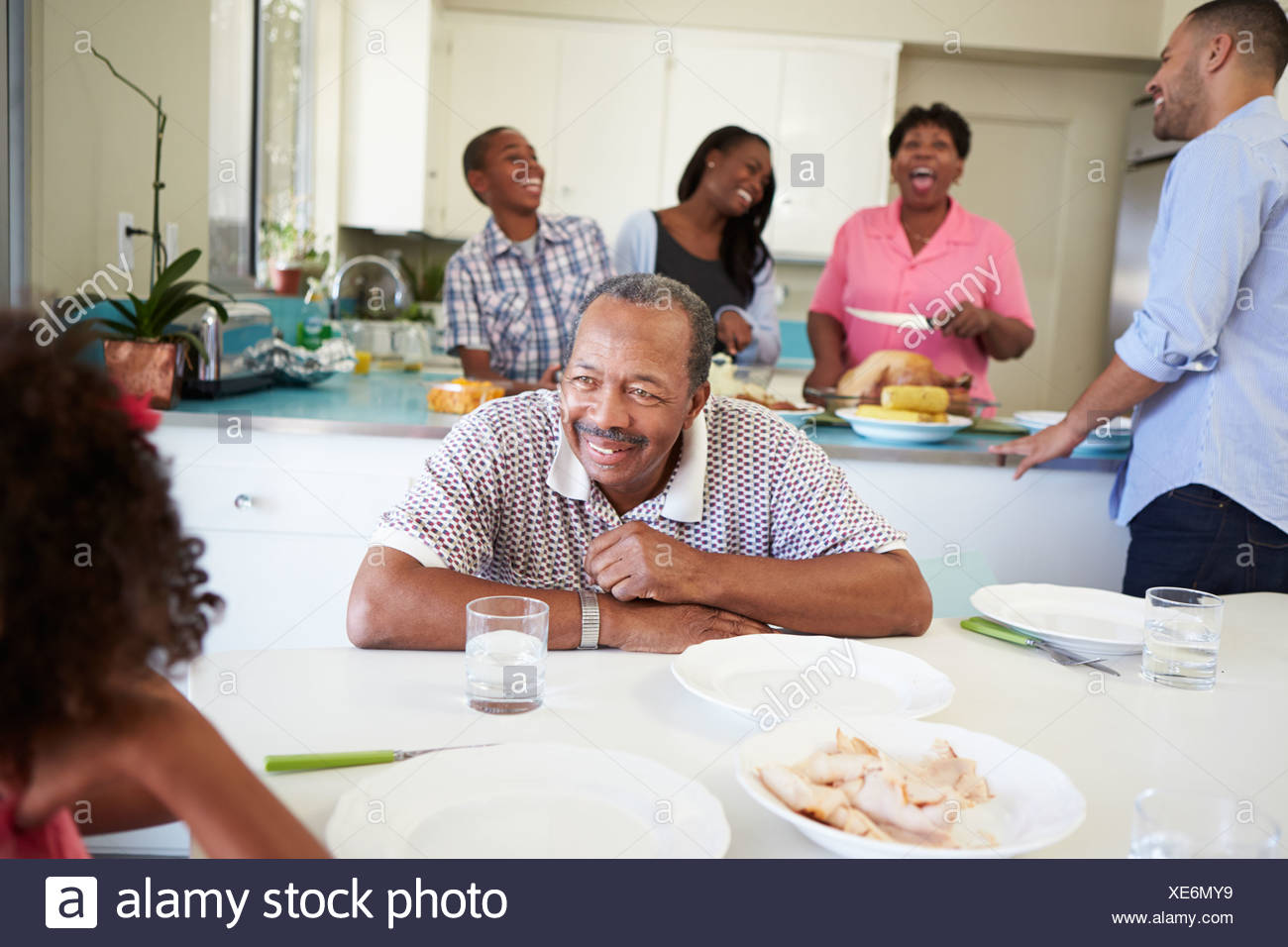 Multi-Generation Family Preparing For Meal At Home - Stock Image