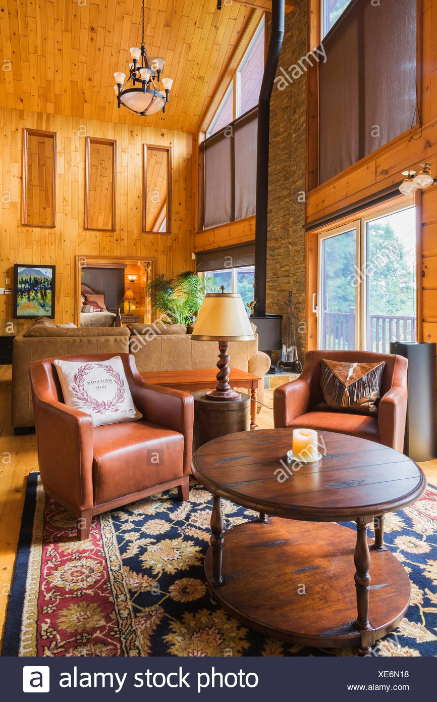 Round Wooden Coffee Table And Reddish Brown Leather Sitting Chairs In  Reading Area Of The Great Room With Cathedral Ceiling Inside A Milled  Cottage Style ...