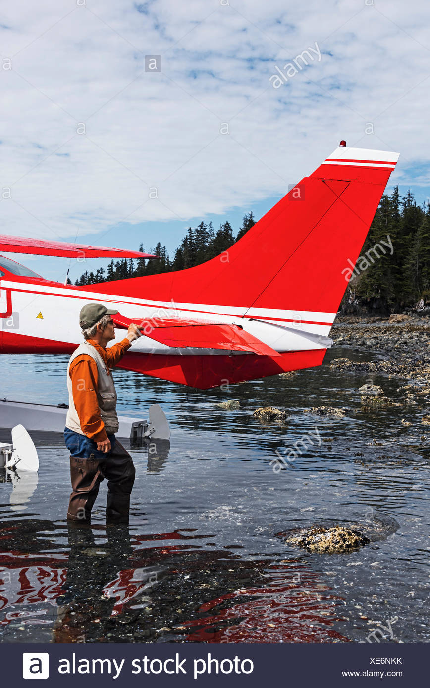 Man standing next to a Cessna 206 float plane in Hobo Bay, Port Wells, Prince William Sound, Southcentral Alaska, USA - Stock Image