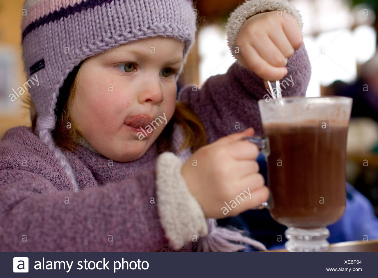 A young girl drinks hot chocolate during a break from skiing at Sunday River in Bethel, Maine. - Stock Image