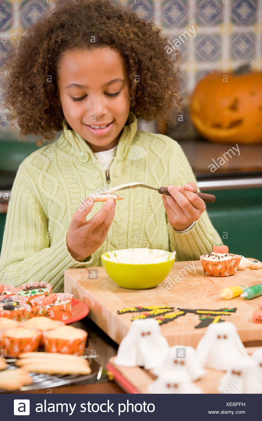 Young girl at Halloween making treats and smiling - Stock Image